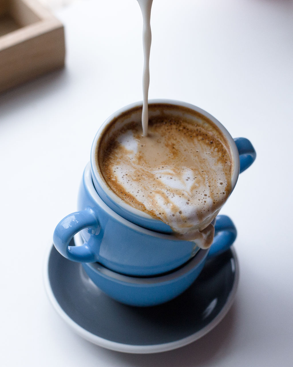 Milk Being Poured In Coffee On Table At Cafe