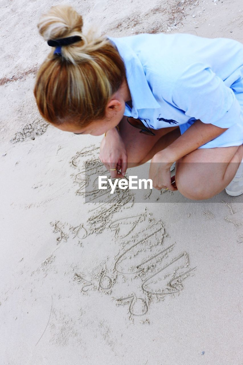 real people, one person, land, high angle view, leisure activity, lifestyles, sand, child, childhood, women, females, creativity, art and craft, beach, drawing - activity, girls, day, nature, hairstyle, innocence