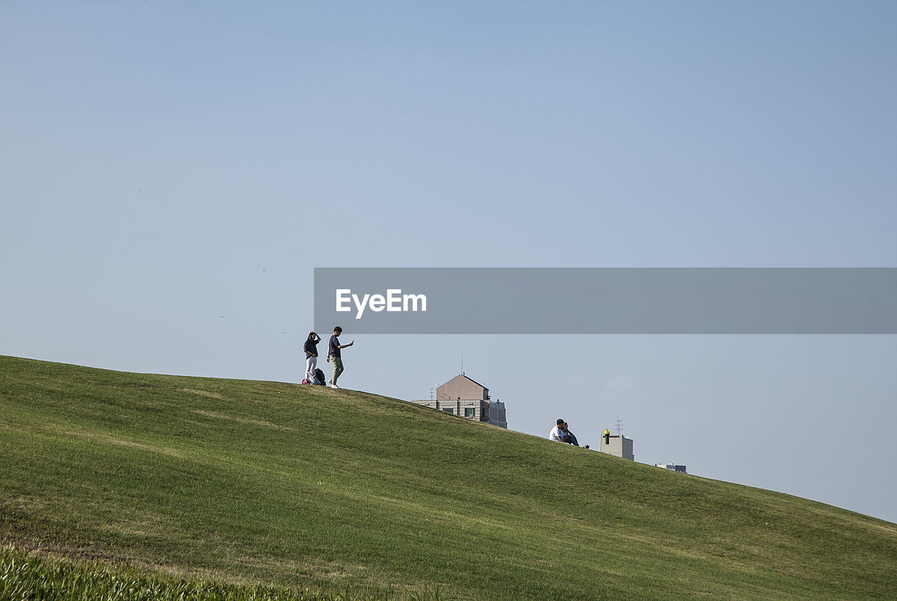 People On Grassy Field Against Sky