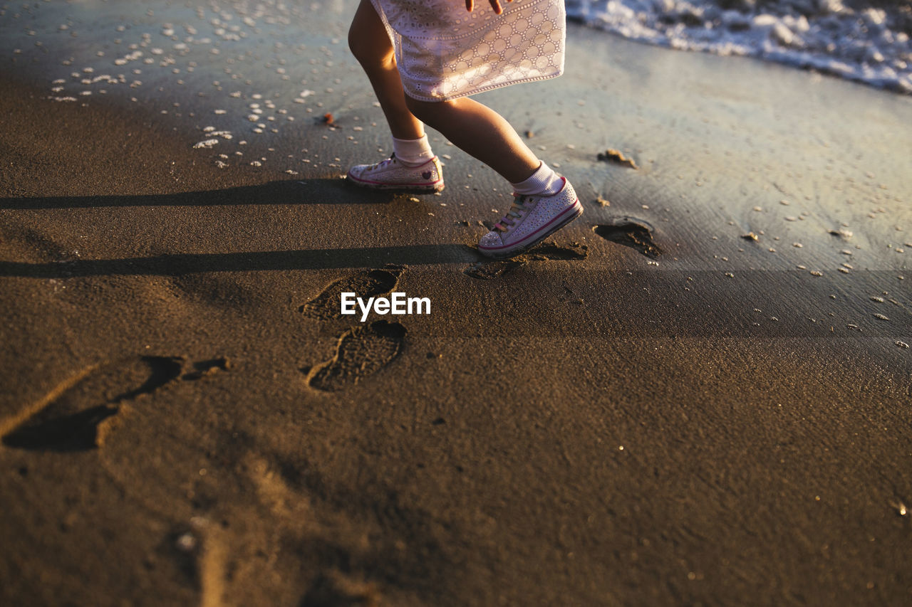 Low Section Of Girl Walking At Beach