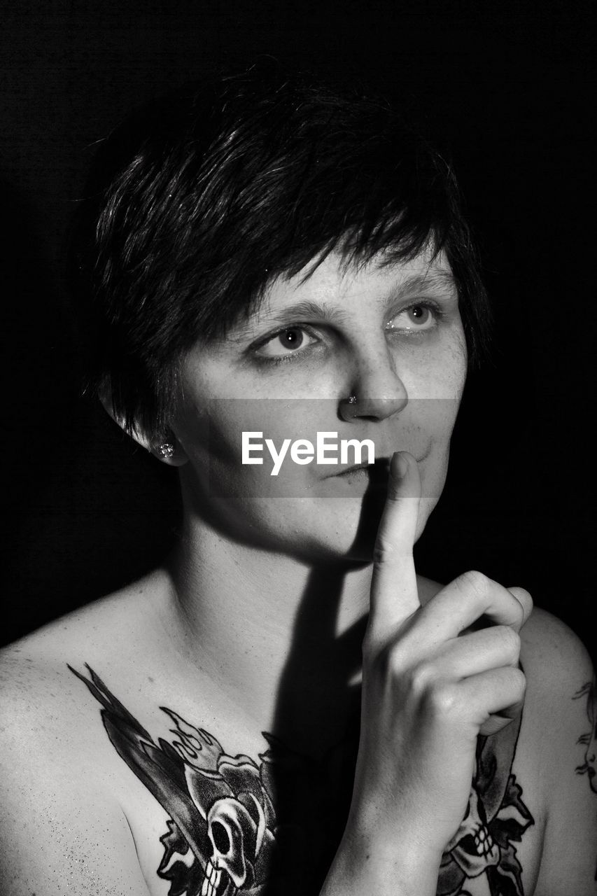 Mid adult tattooed woman with finger on lips against black background