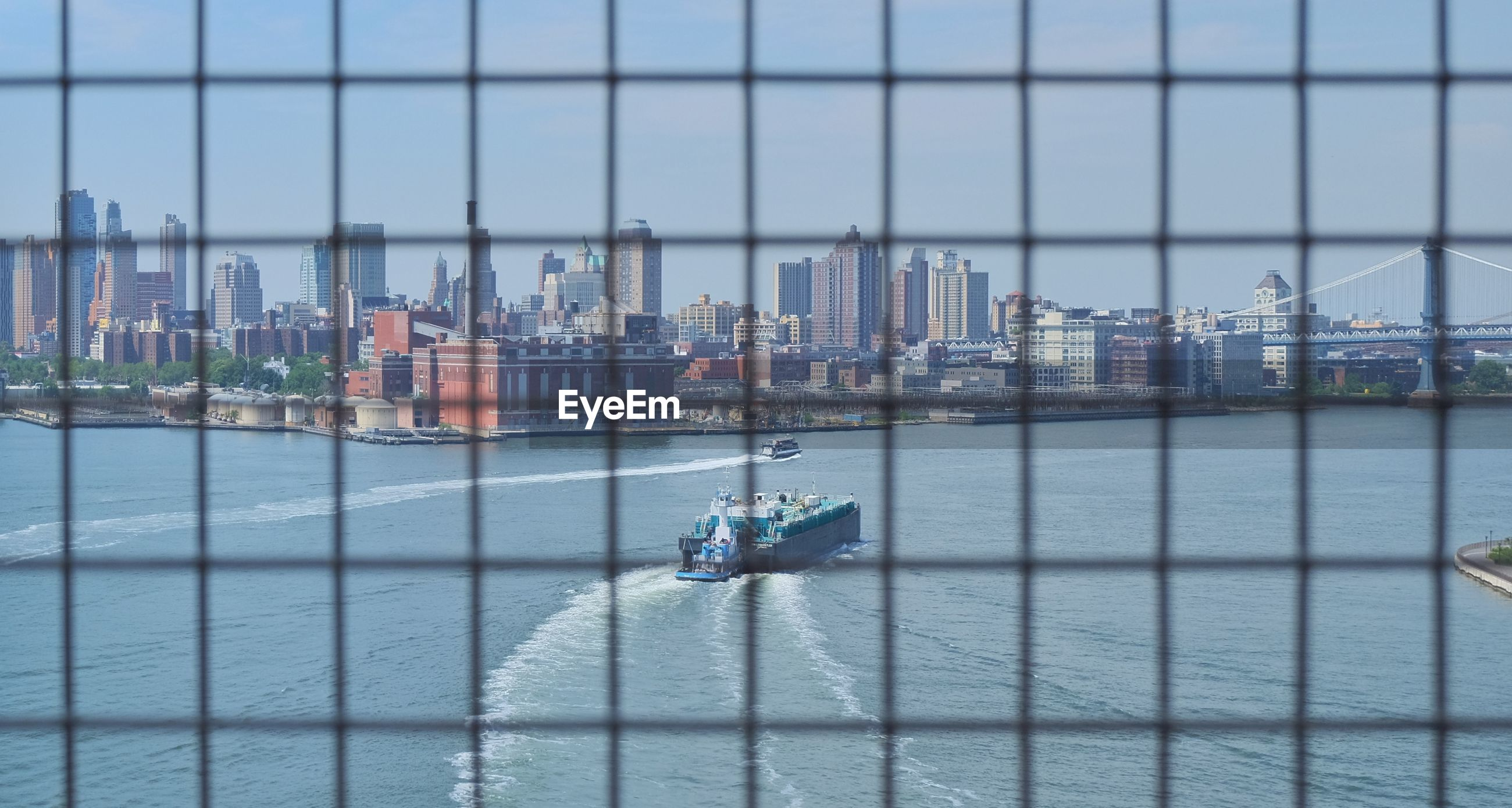 Ship sailing in sea by city skyline seen through fence