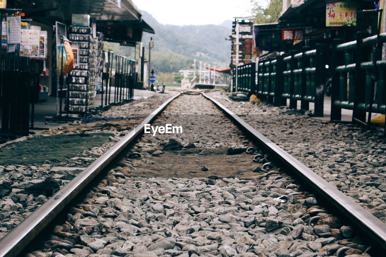 rail transportation, track, railroad track, direction, transportation, the way forward, architecture, diminishing perspective, built structure, solid, nature, vanishing point, building exterior, stone - object, gravel, rock, no people, day, mode of transportation, outdoors, pebble, long, surface level, parallel