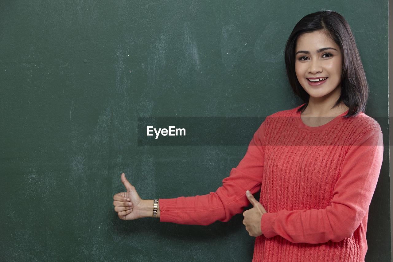 Portrait of happy female teacher gesturing thumbs up by blackboard