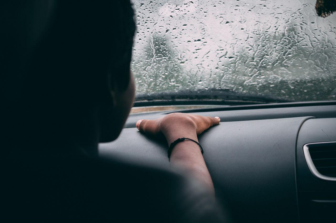 Boy sitting in car during rainy season