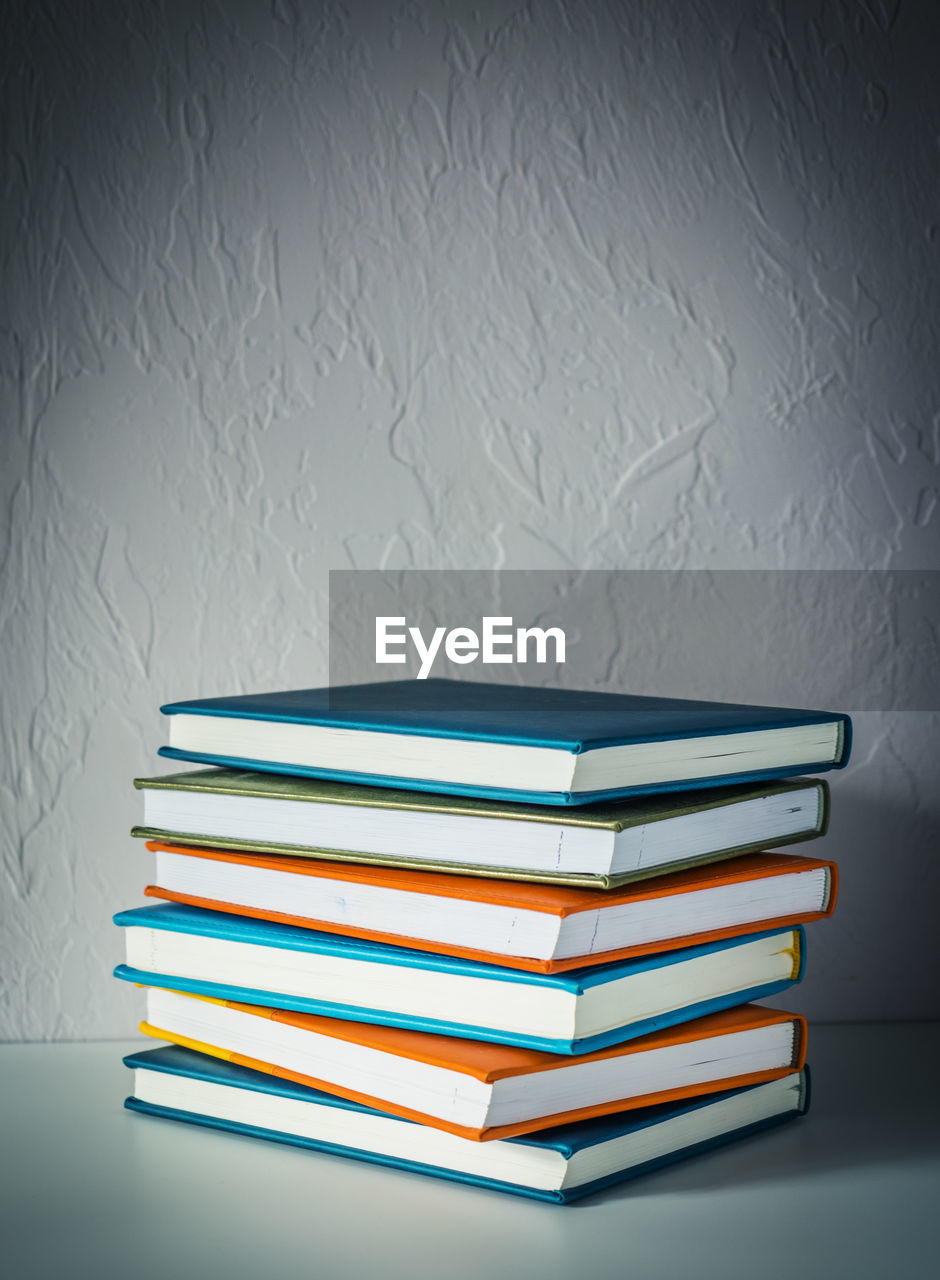 publication, book, education, stack, indoors, table, wall - building feature, learning, no people, still life, large group of objects, close-up, white color, wisdom, literature, group of objects, expertise, choice, variation, hardcover book, textbook