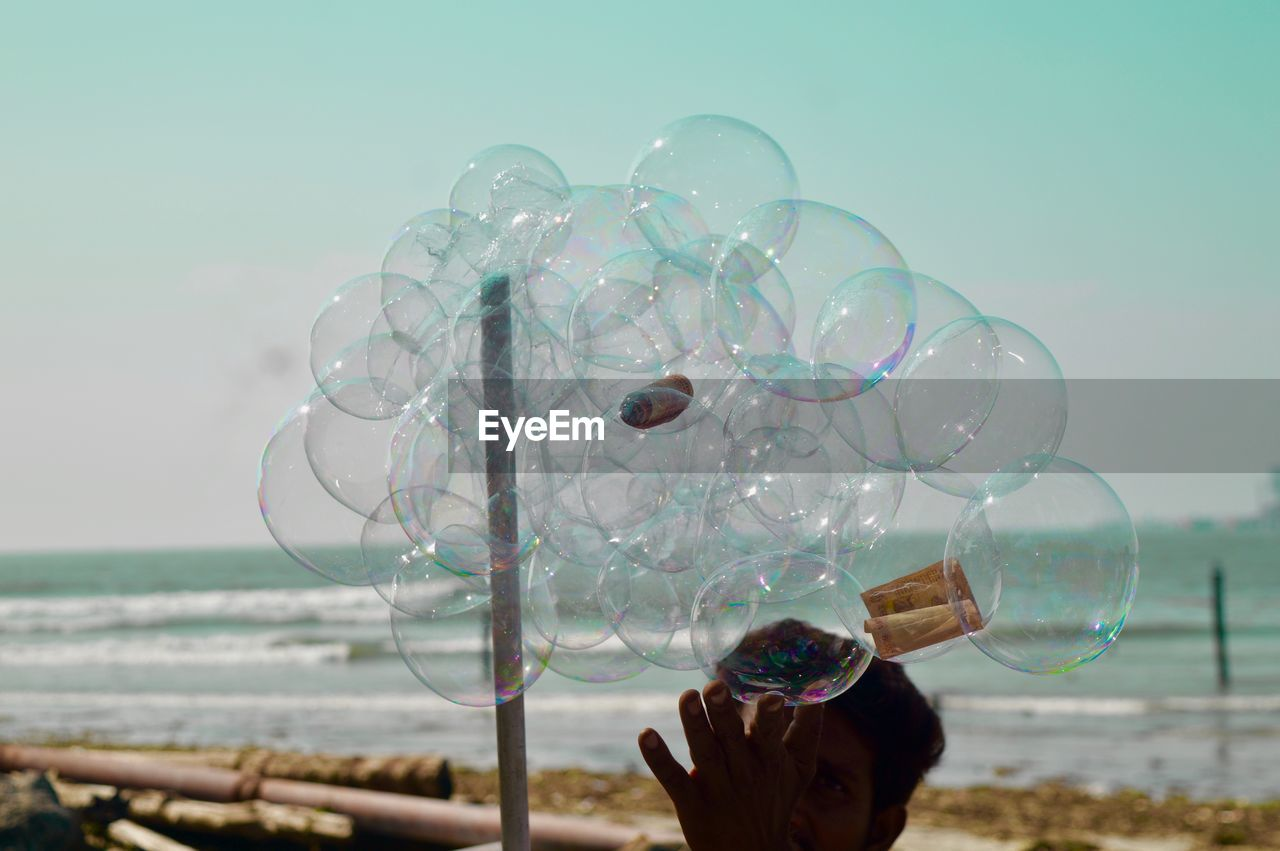 water, one person, bubble, holding, real people, nature, human hand, hand, sea, bubble wand, sky, human body part, land, lifestyles, day, transparent, fragility, vulnerability, outdoors, finger