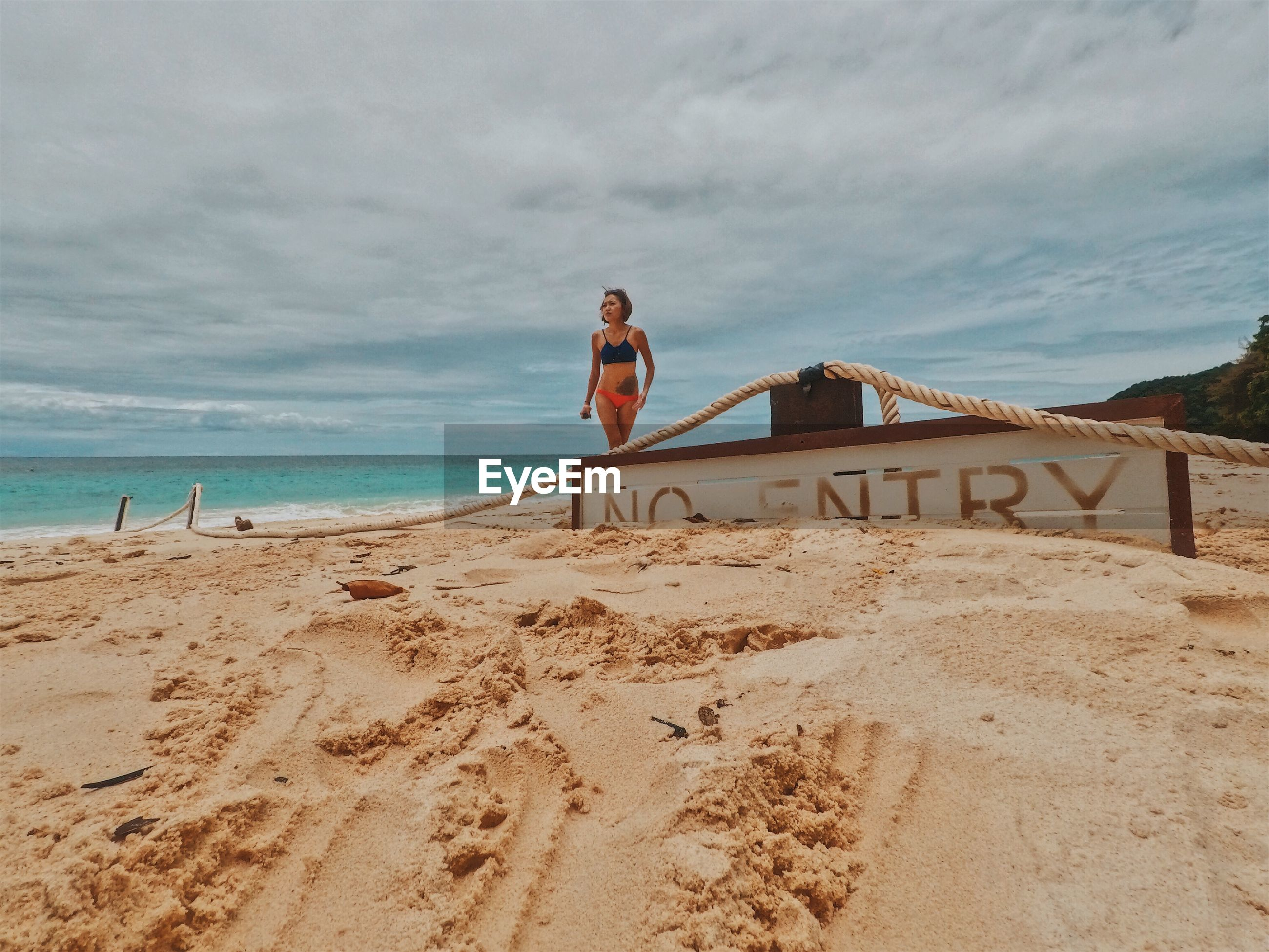 Woman in bikini walking on shore by no entry text at beach against cloudy sky