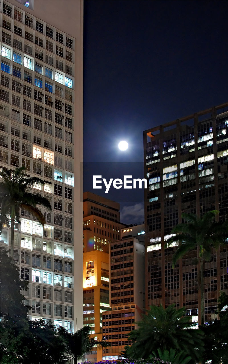 night, architecture, building exterior, illuminated, city, built structure, modern, skyscraper, no people, moon, outdoors, clear sky, sky, cityscape