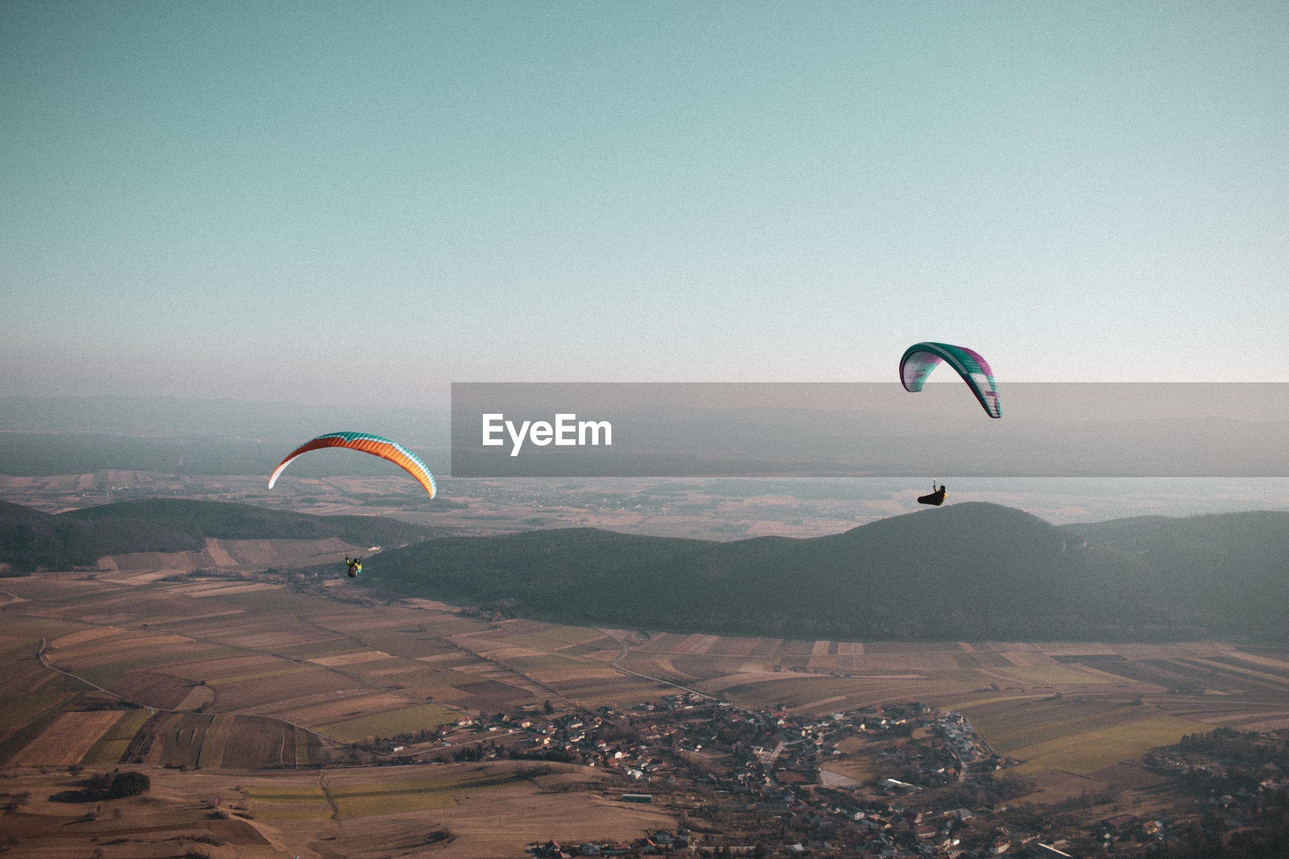 PEOPLE FLYING KITE AGAINST SKY