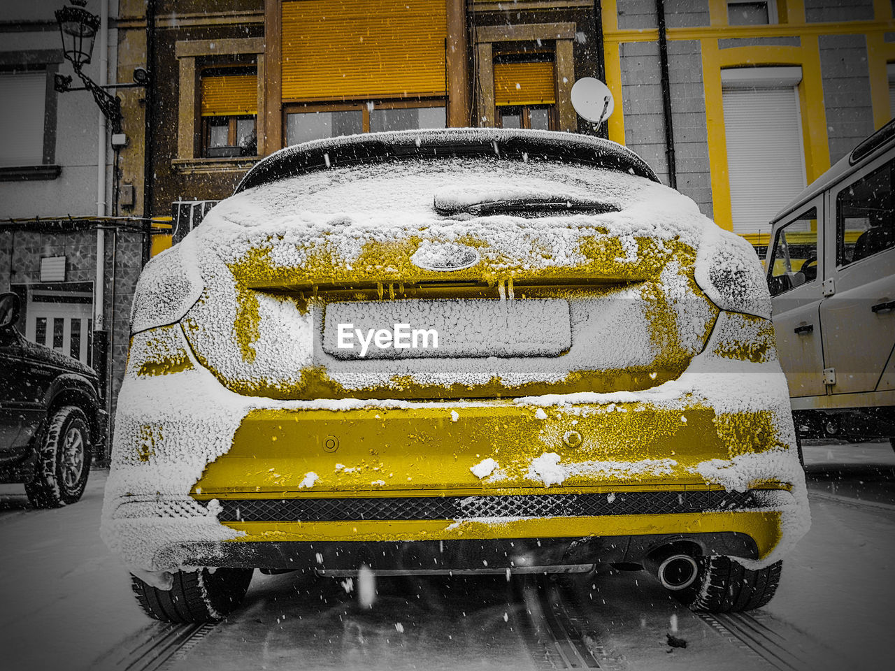 CLOSE-UP OF YELLOW CAR ON SNOW COVERED CARS