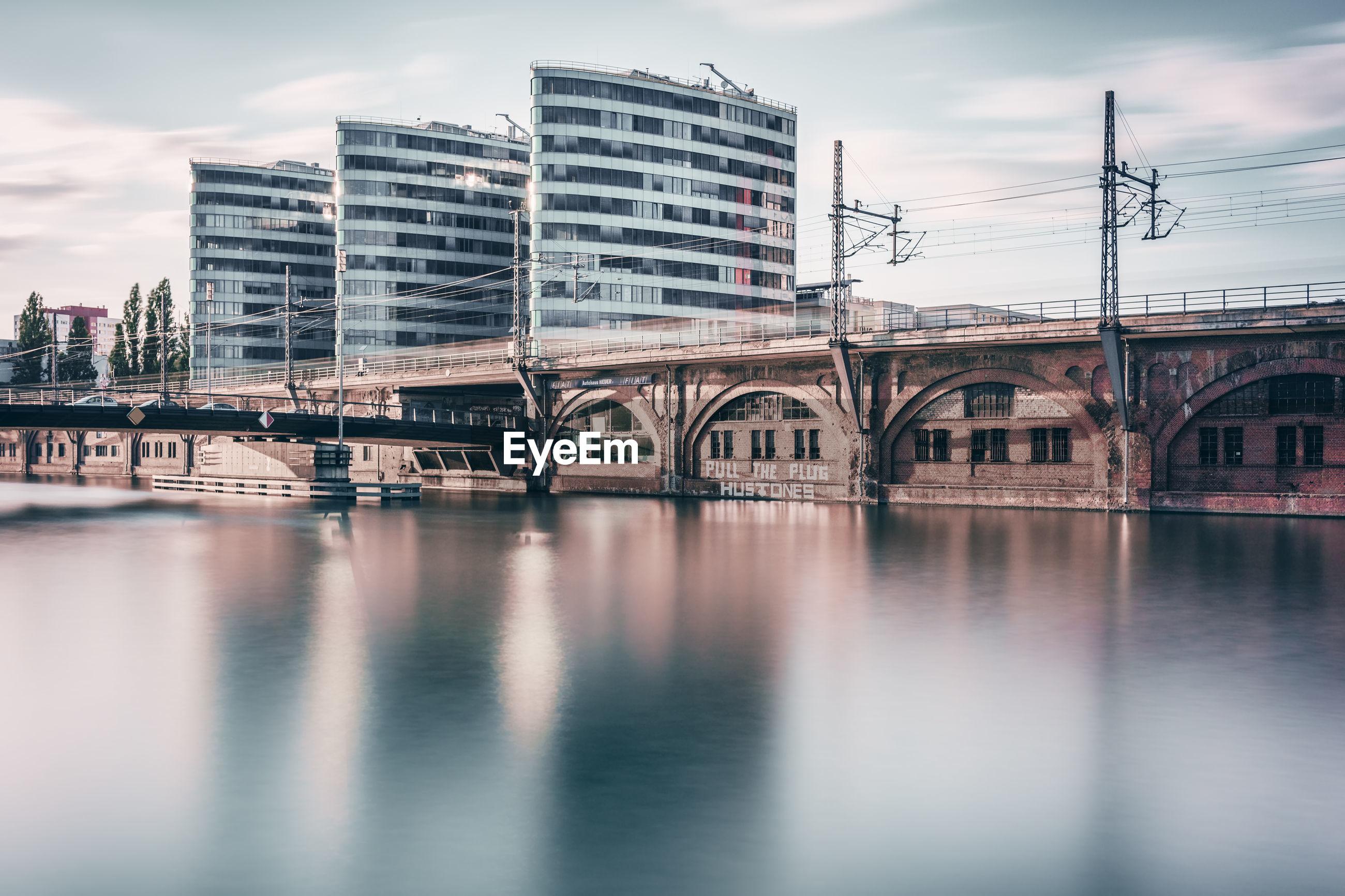 River by bridge against buildings in city