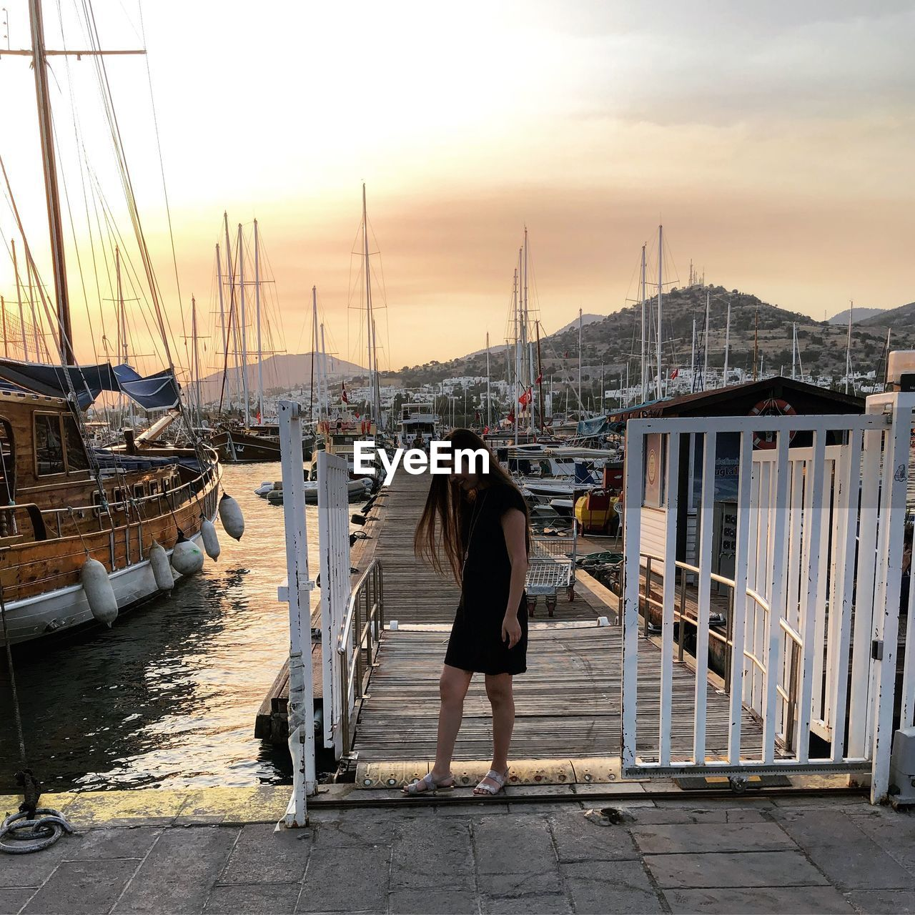Full Length Of Woman Standing At Harbor Against Sky During Sunset