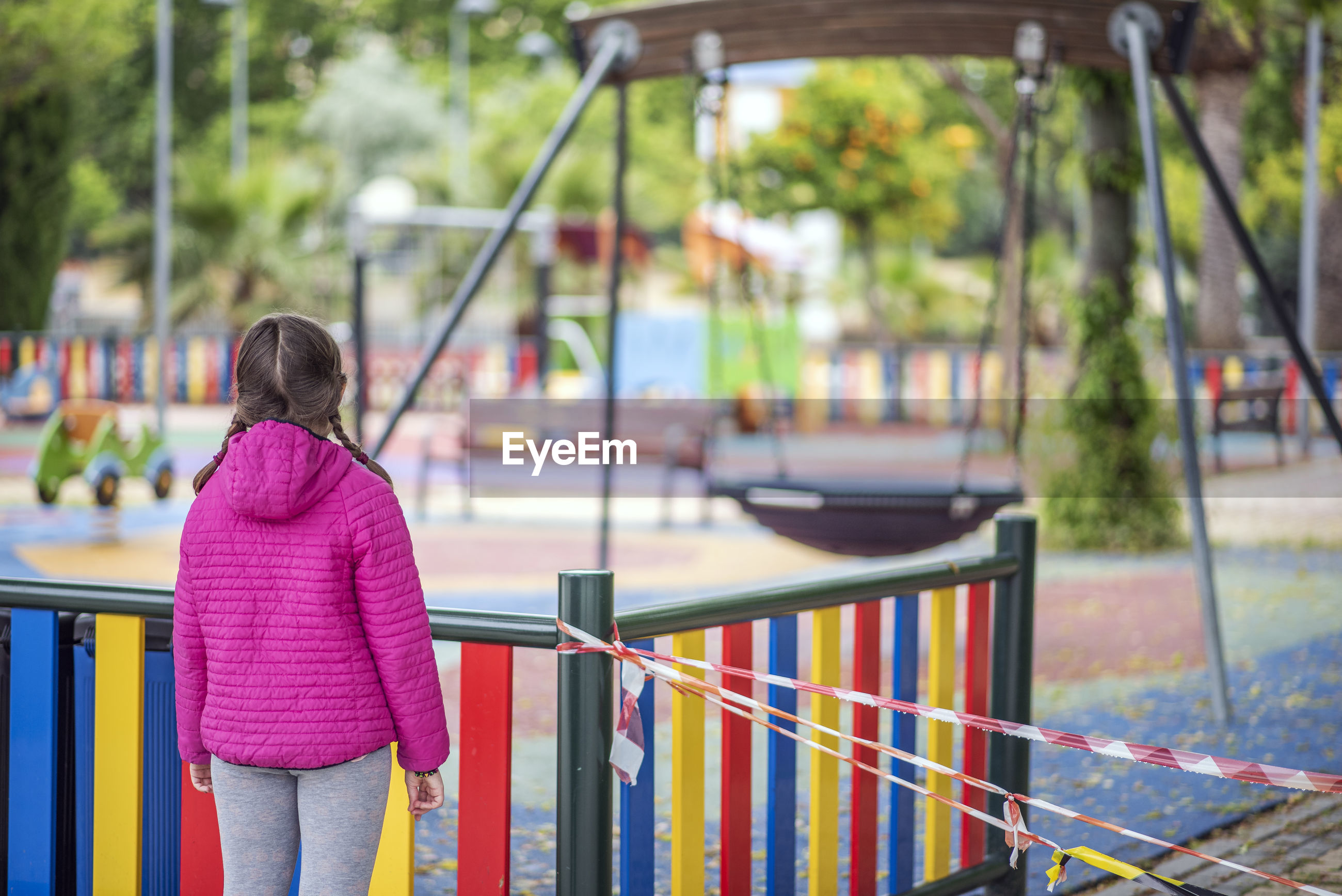REAR VIEW OF WOMAN STANDING BY RAILING AGAINST PLAYGROUND