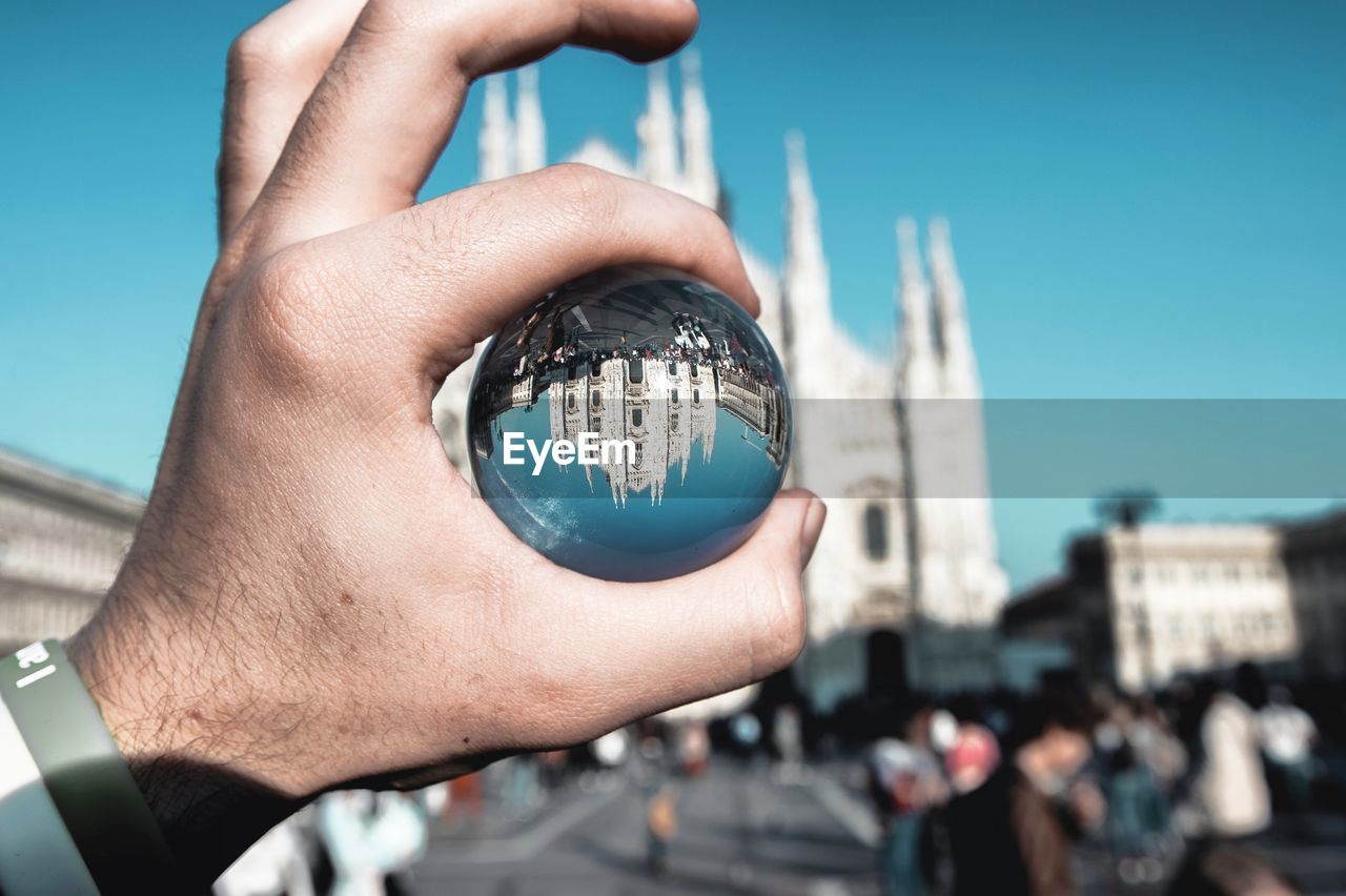 human hand, hand, holding, focus on foreground, real people, architecture, building exterior, built structure, human body part, sky, city, day, lifestyles, one person, sunlight, nature, tower, body part, unrecognizable person, finger, outdoors, office building exterior