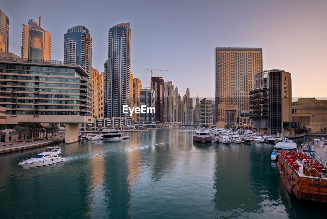 building exterior, water, built structure, architecture, nautical vessel, transportation, mode of transportation, city, building, sky, office building exterior, waterfront, moored, skyscraper, river, nature, tall - high, office, no people, modern, harbor, cityscape, outdoors, yacht, financial district, passenger craft