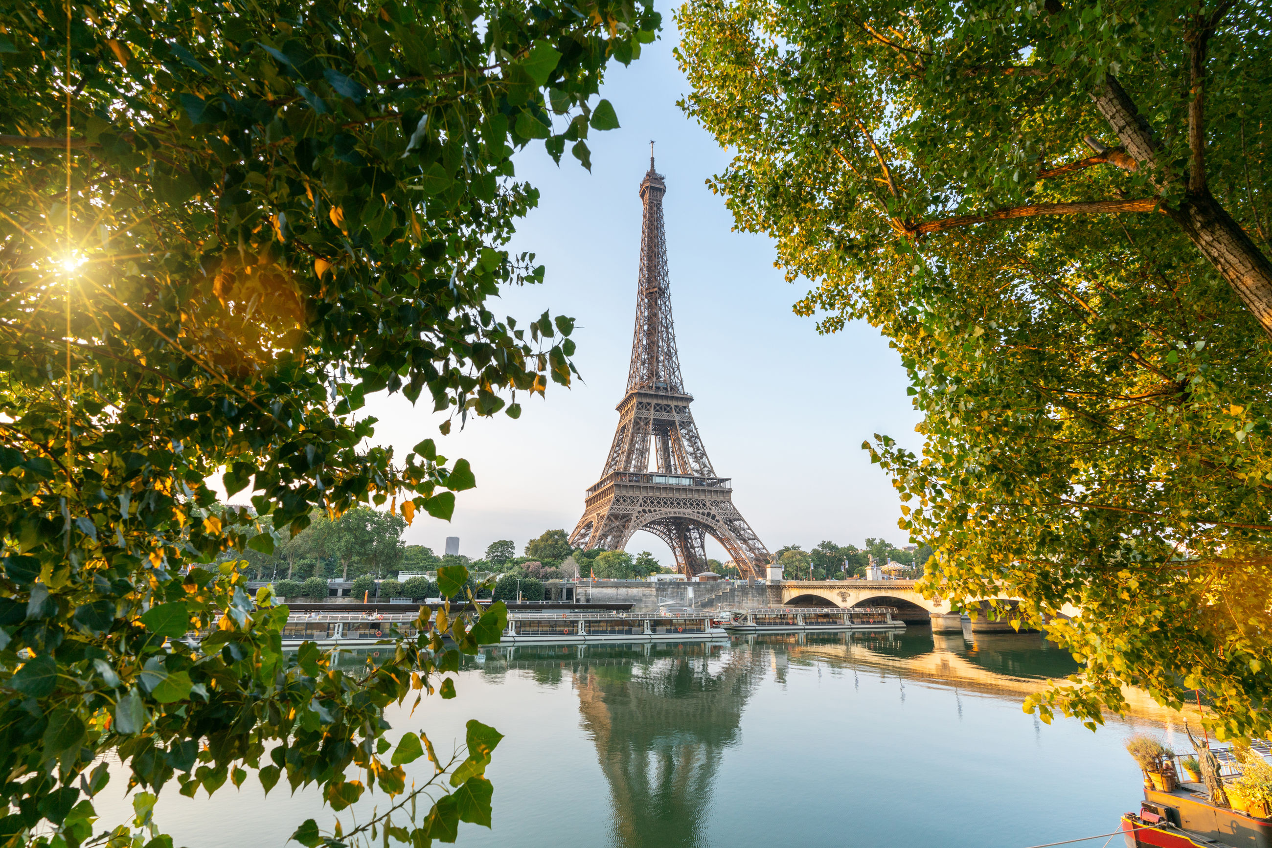Eiffel tower by river against clear sky