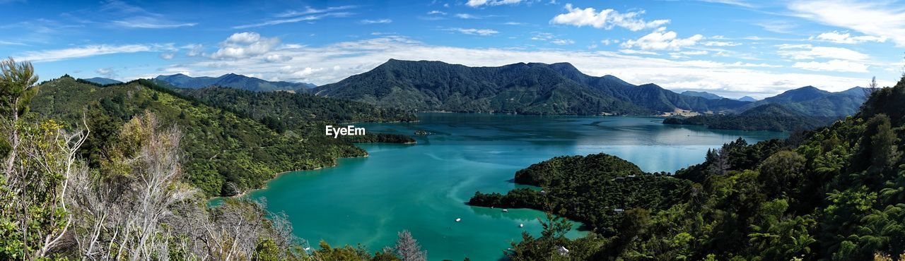 Scenic View Of Lake In Mountains Against Sky
