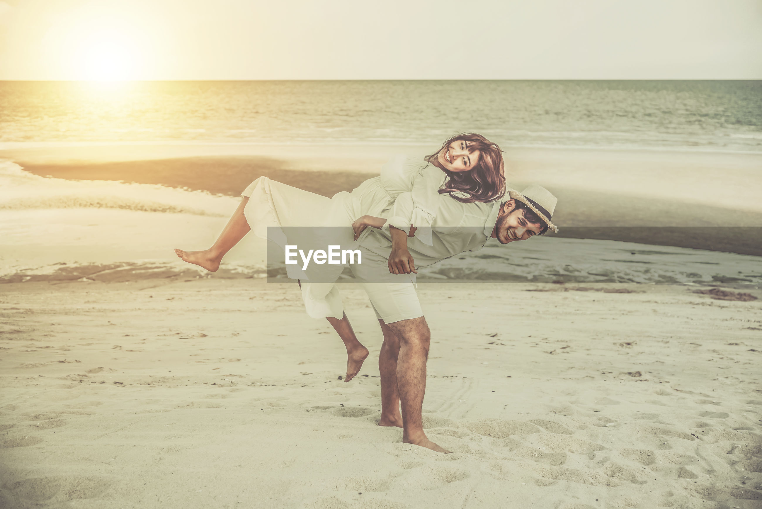 Couple enjoying at beach during sunset