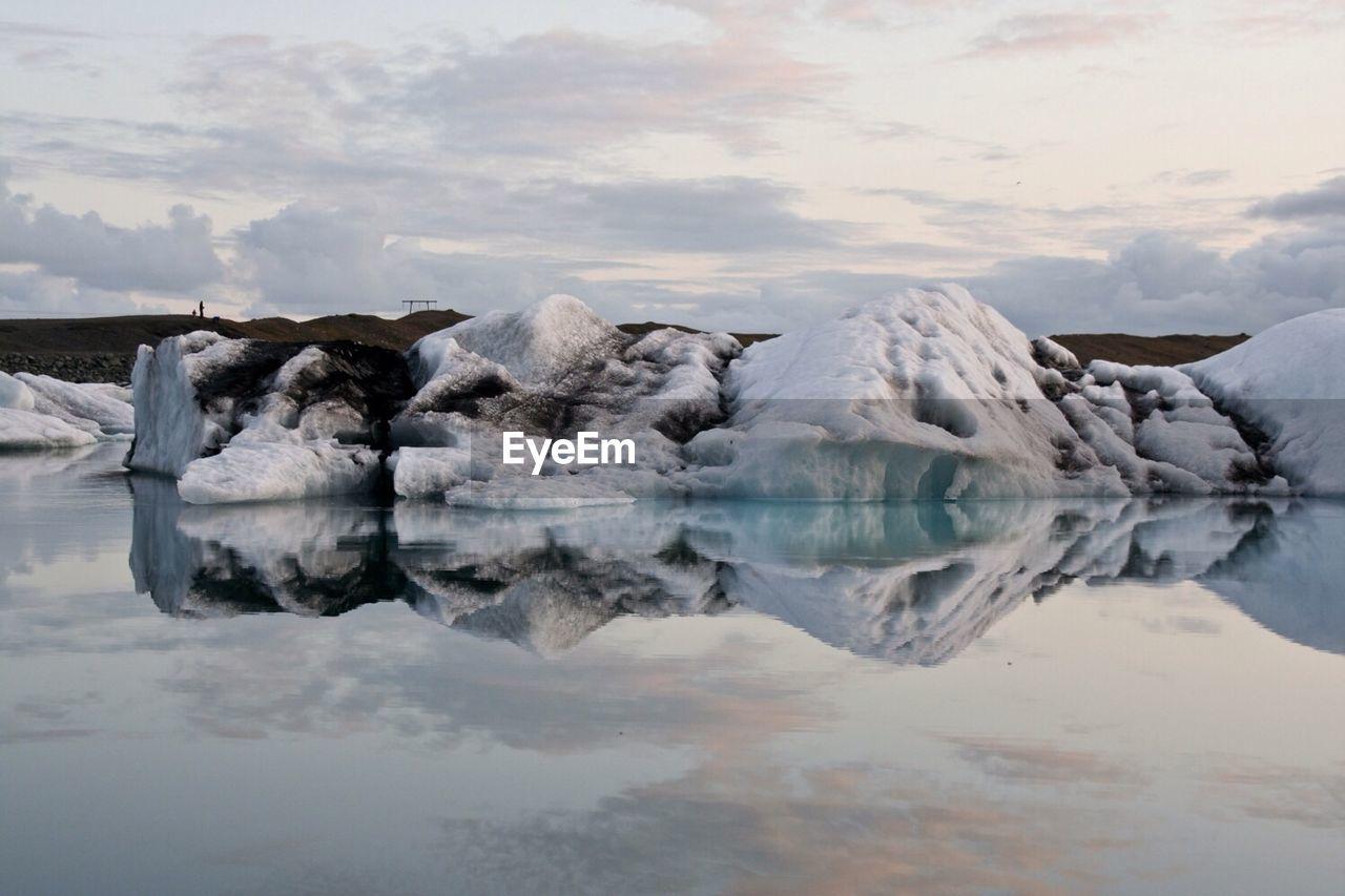 Rocks At Lake Against Cloudy Sky