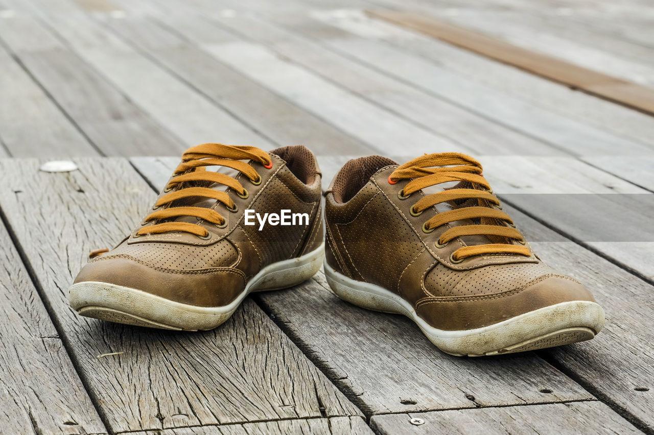 Close-up of brown shoe on wooden platform