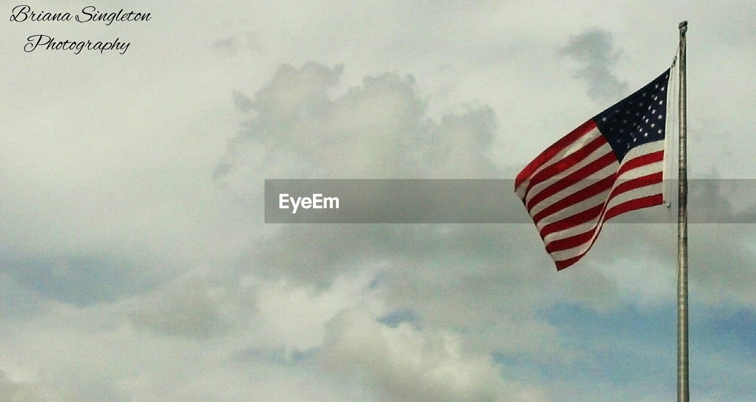 patriotism, flag, identity, national flag, american flag, low angle view, sky, wind, striped, cloud - sky, culture, pride, pole, cloud, flag pole, star shape, red, waving, outdoors, cloudy