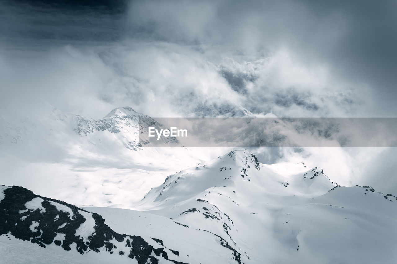 cloud - sky, cold temperature, mountain, winter, snow, beauty in nature, scenics - nature, sky, tranquil scene, tranquility, white color, snowcapped mountain, nature, non-urban scene, day, mountain range, environment, no people, covering, outdoors, mountain peak, extreme weather