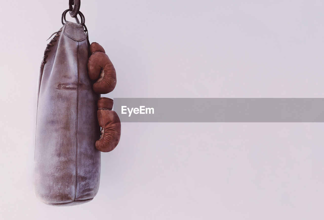 Punching Bag Hanging With Boxing Gloves By White Wall