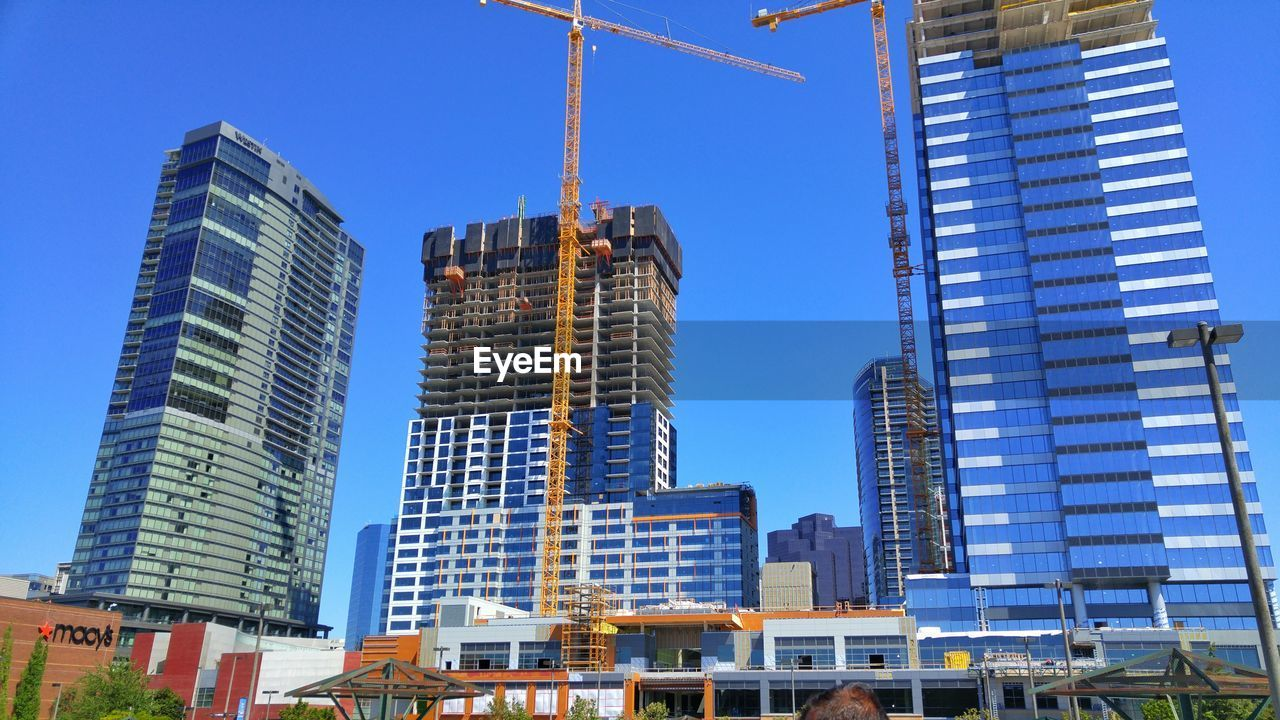 architecture, skyscraper, built structure, building exterior, blue, tall - high, low angle view, city, modern, tower, development, clear sky, day, sky, outdoors, construction site, tall, no people, urban skyline, office park, cityscape