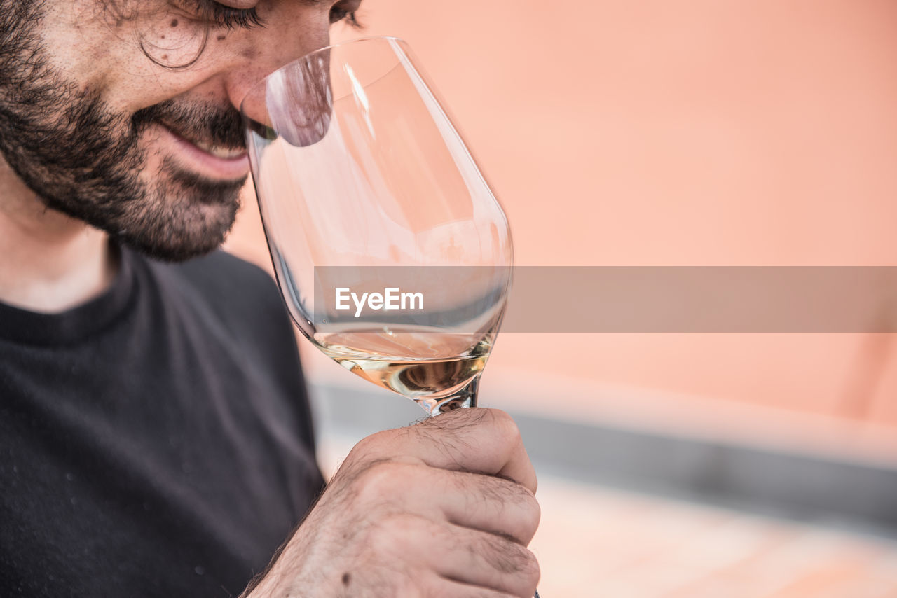 Close-up of smiling man smelling wine