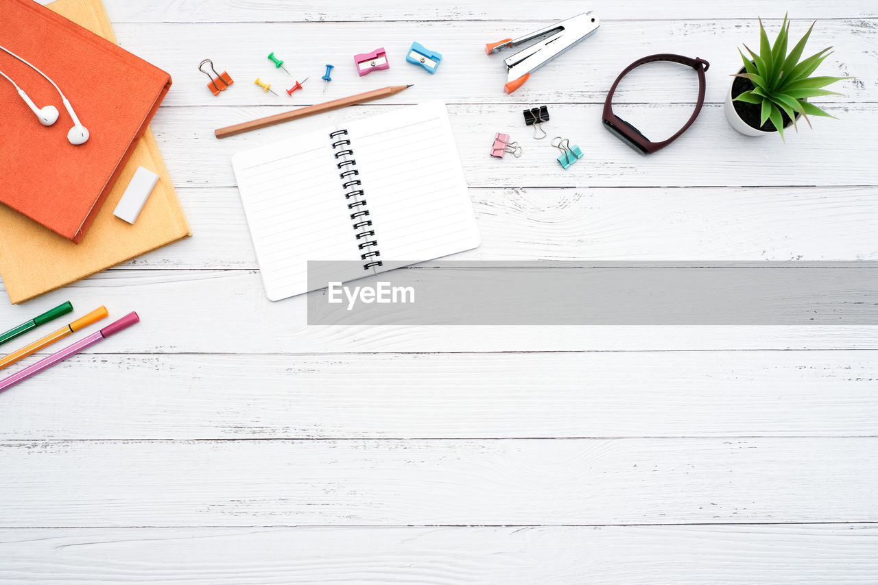 table, still life, paper, pencil, pen, education, publication, indoors, book, wood - material, note pad, high angle view, no people, office supply, writing instrument, directly above, page, office, white color, clip, school supplies, blank
