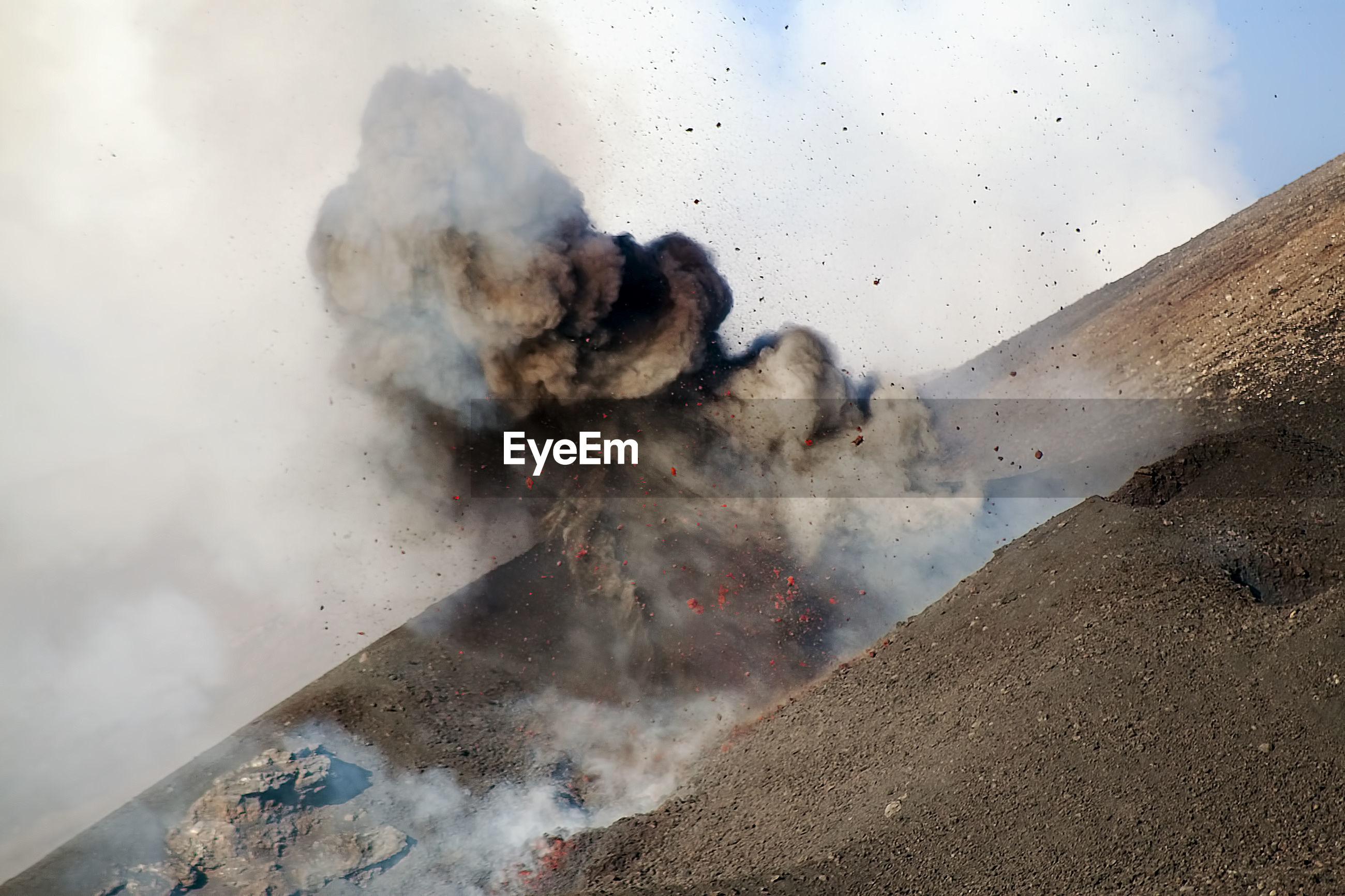 Volcano exploding against sky