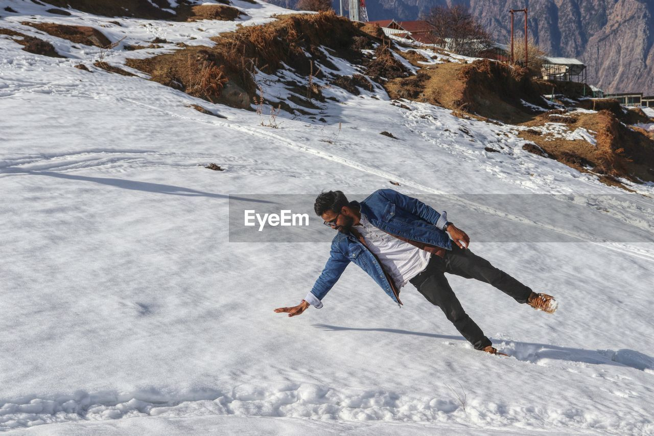 Full length of man falling on snow covered mountain during winter