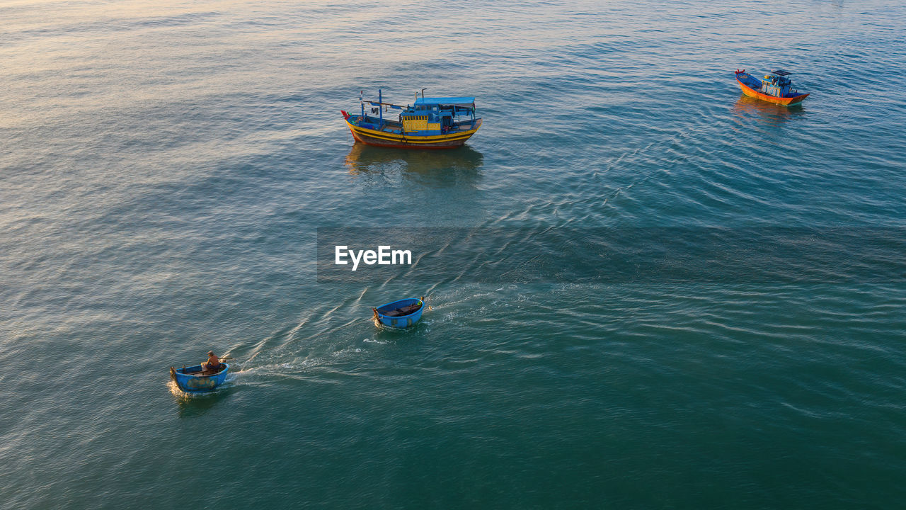 HIGH ANGLE VIEW OF MEN IN SEA
