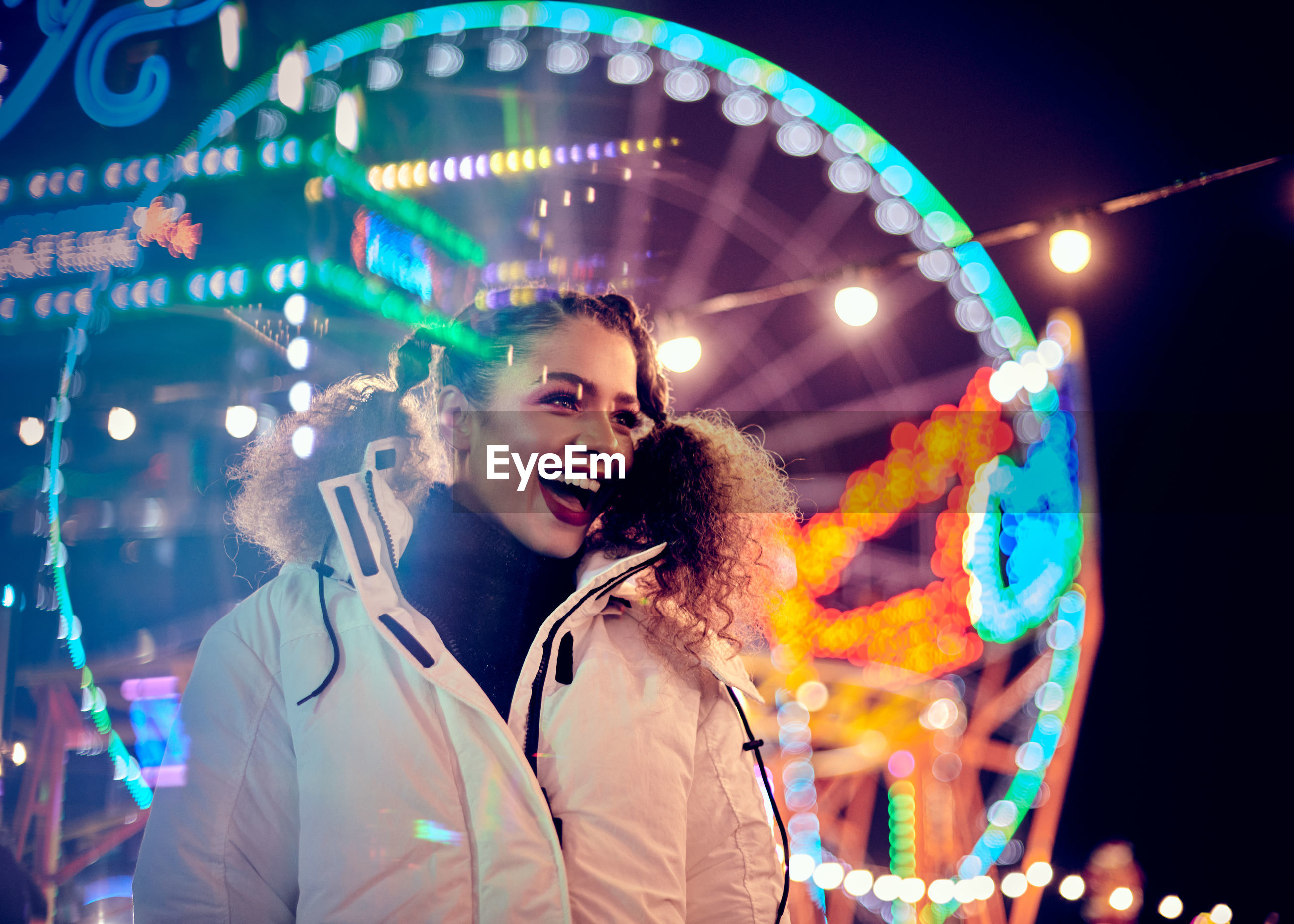 Happy woman standing against illuminated ferris wheel at night