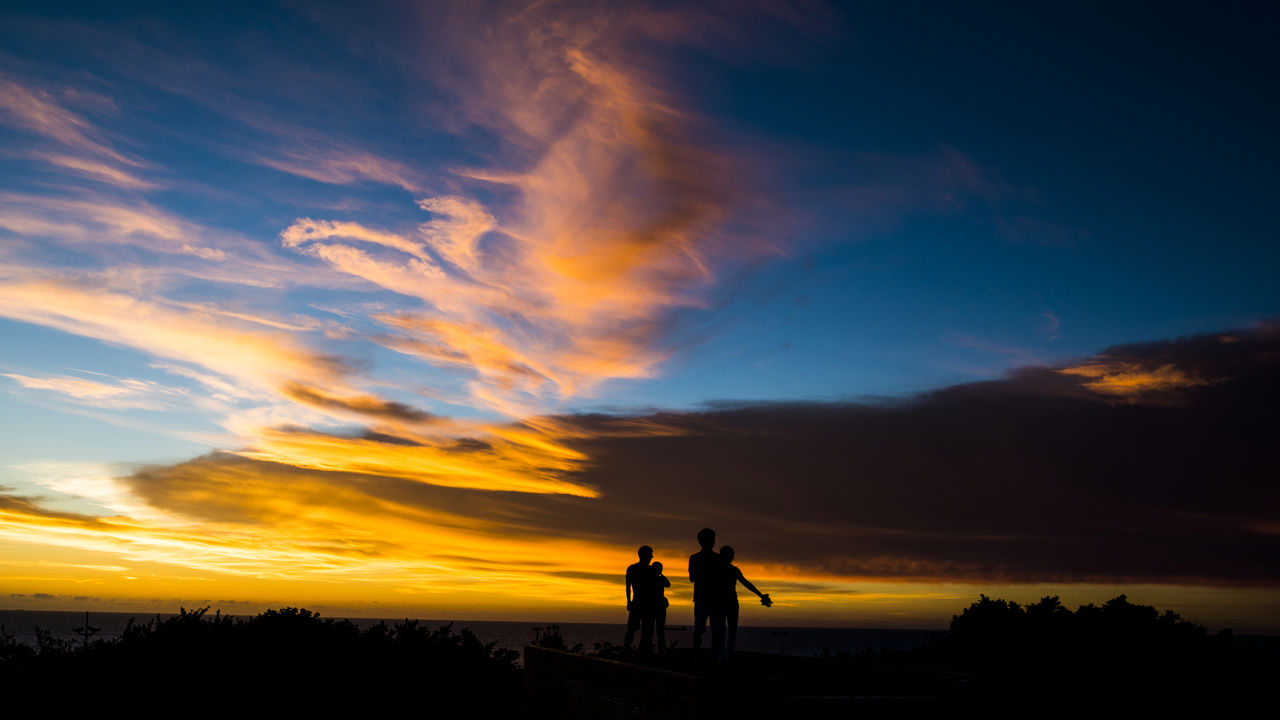 Silhouette People Standing On Landscape Against Sky During Sunset
