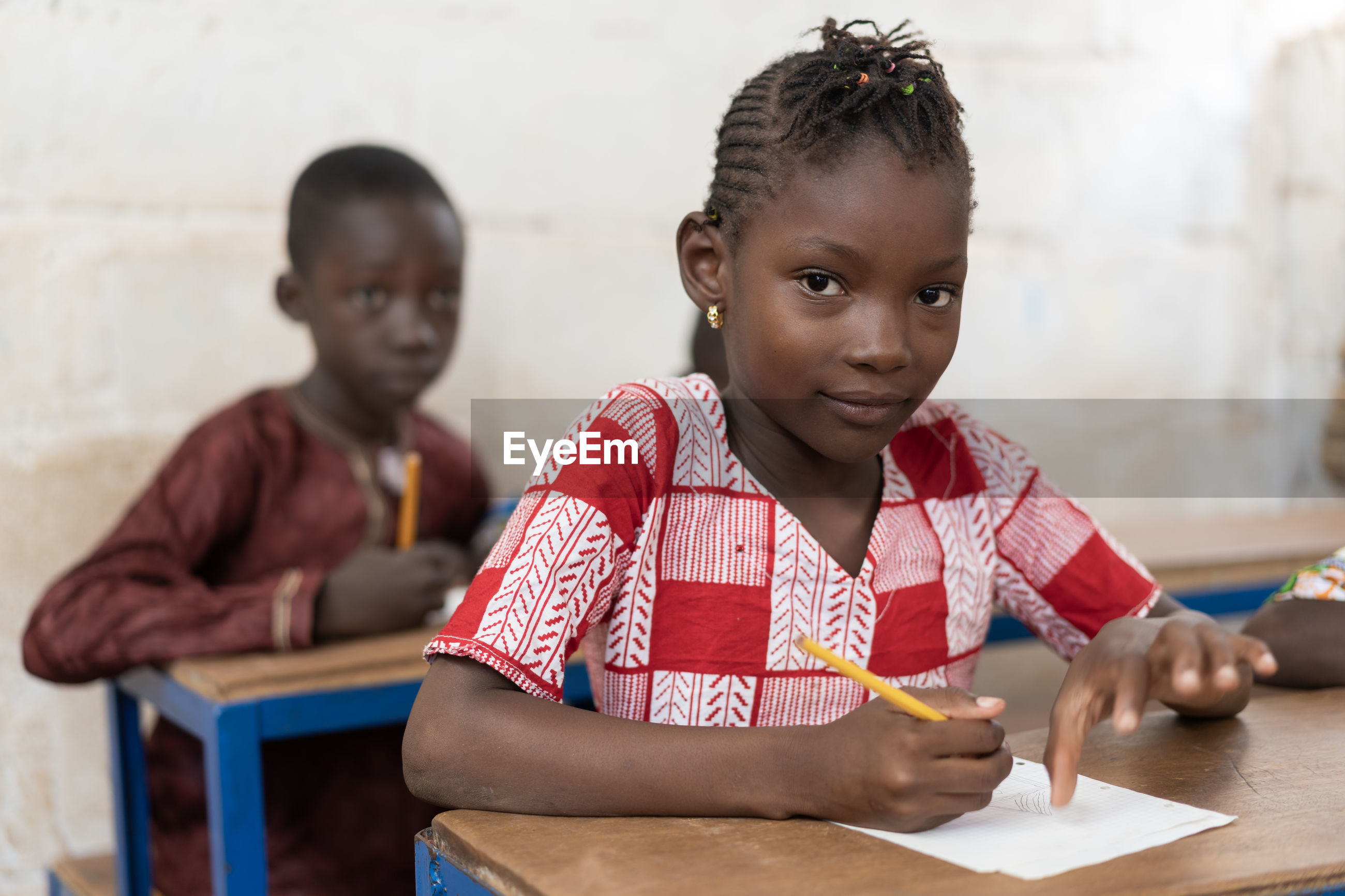 Portrait of girl writing at table in classroom