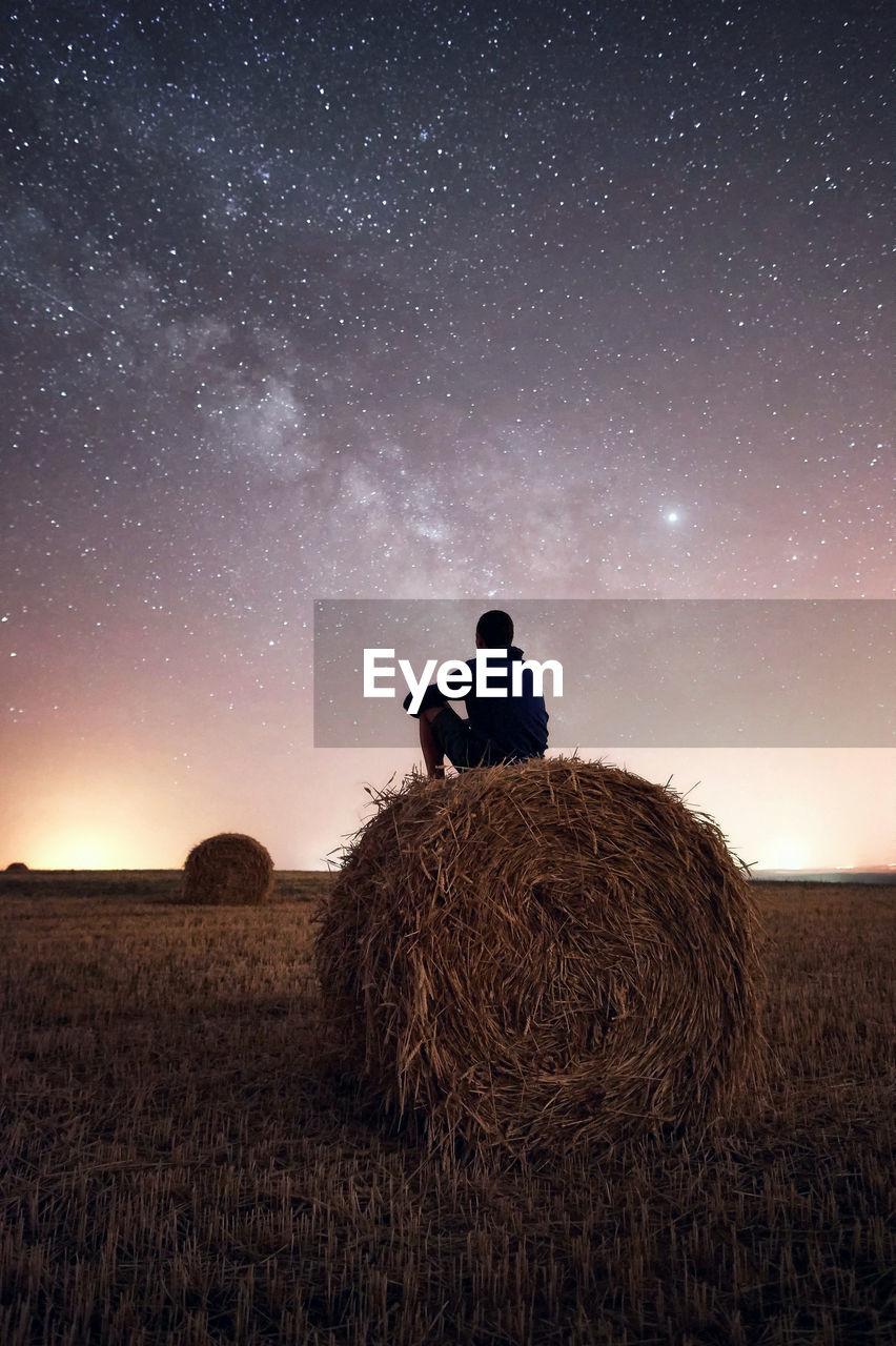 sky, field, one person, rear view, land, real people, star - space, night, men, bale, scenics - nature, beauty in nature, hay, space, nature, plant, lifestyles, landscape, farm, astronomy, outdoors