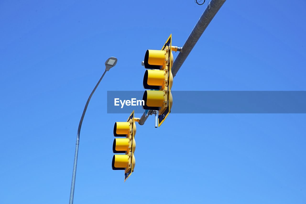 Low Angle View Of Road Signal Against Clear Blue Sky