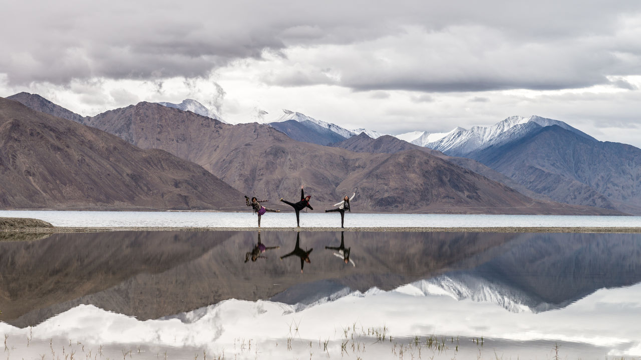Reflection Of Mountains And People In Pangong Lake Against Cloudy Sky