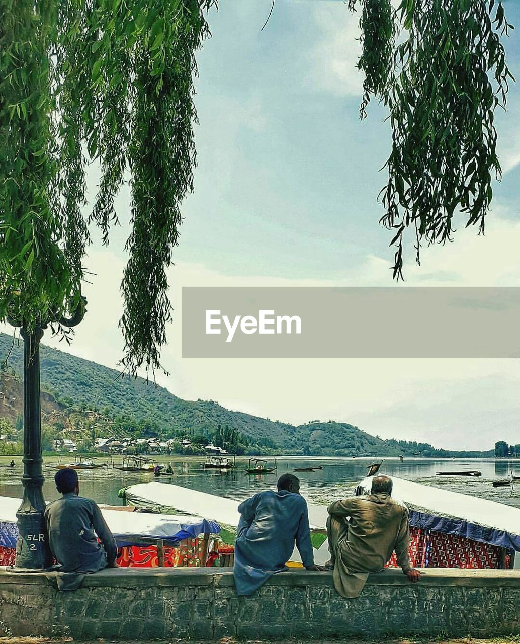 tree, rear view, real people, sky, men, transportation, cloud - sky, day, mode of transport, nature, sitting, mountain, outdoors, women, casual clothing, togetherness, lifestyles, water, scenics, mountain range, lake, nautical vessel, beauty in nature, people