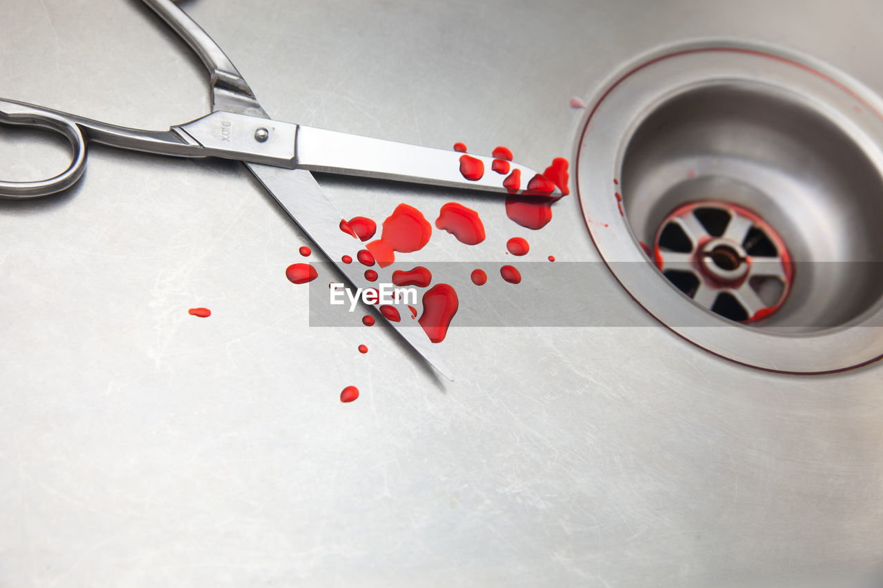High angle view of scissor with blood drops at sink