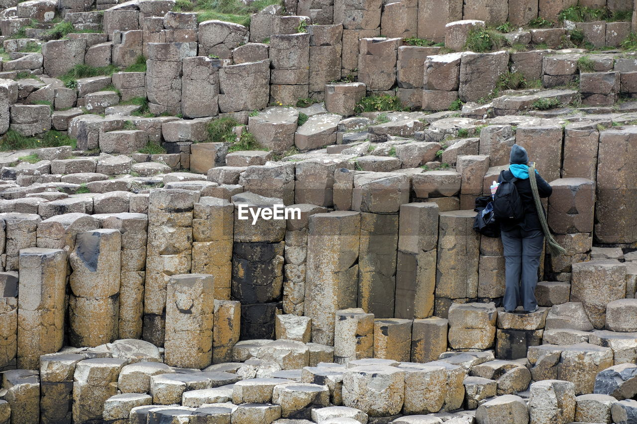 one person, solid, day, leisure activity, architecture, full length, men, real people, lifestyles, rear view, history, the past, rock - object, nature, rock, built structure, tourism, standing, outdoors, stone wall, warm clothing