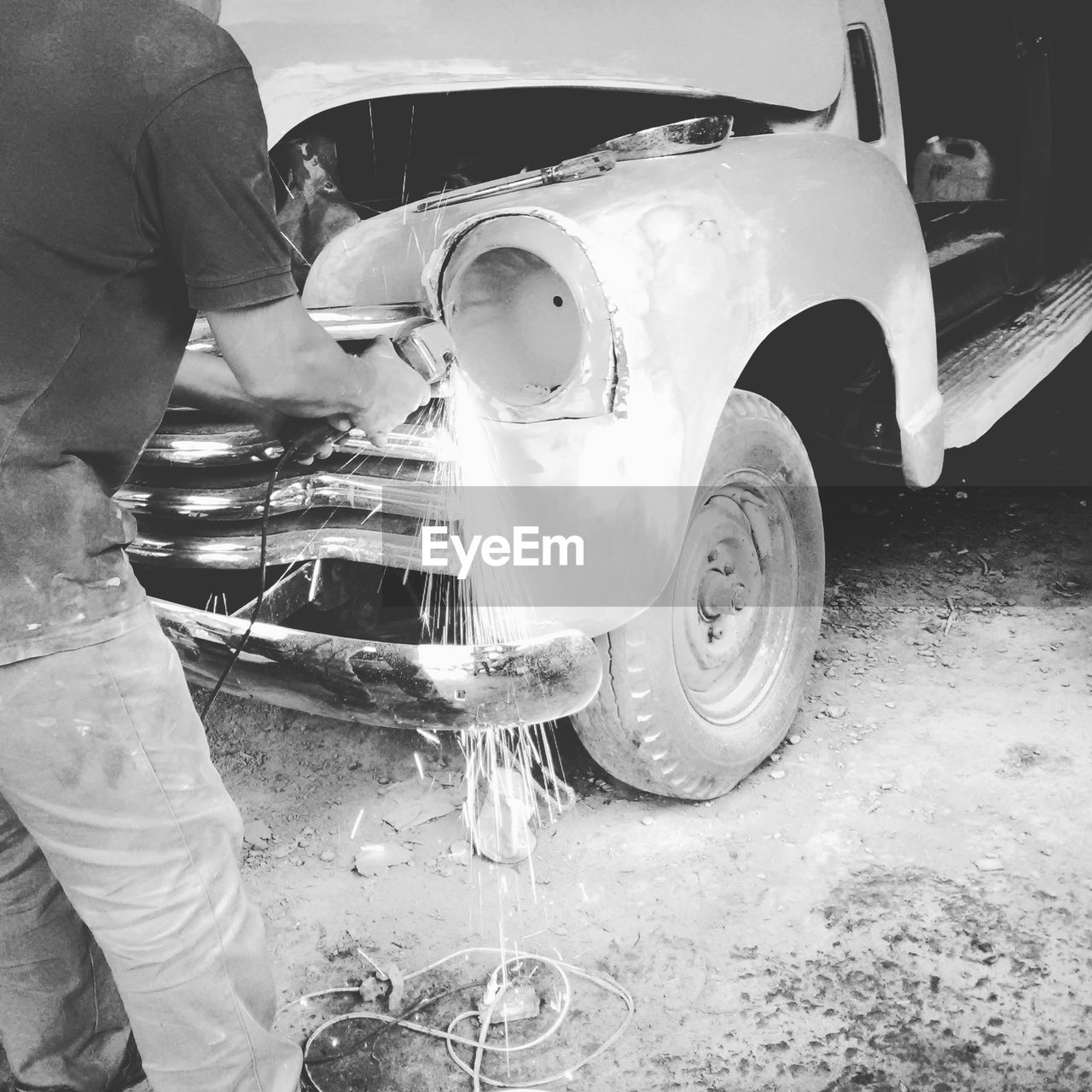 Low section of worker repairing old vintage car
