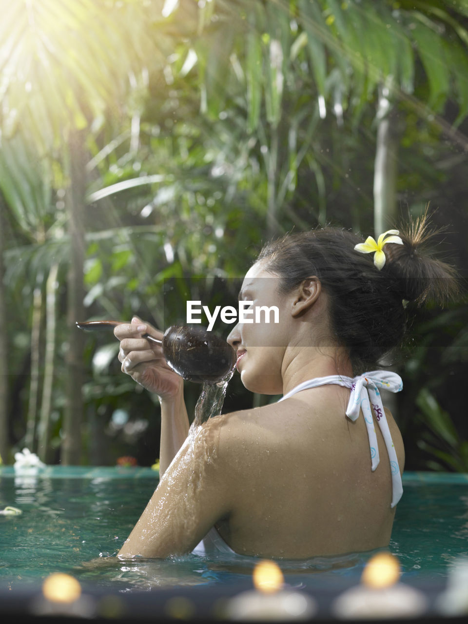 Woman Taking Bath With Ladle In Pool Against Trees