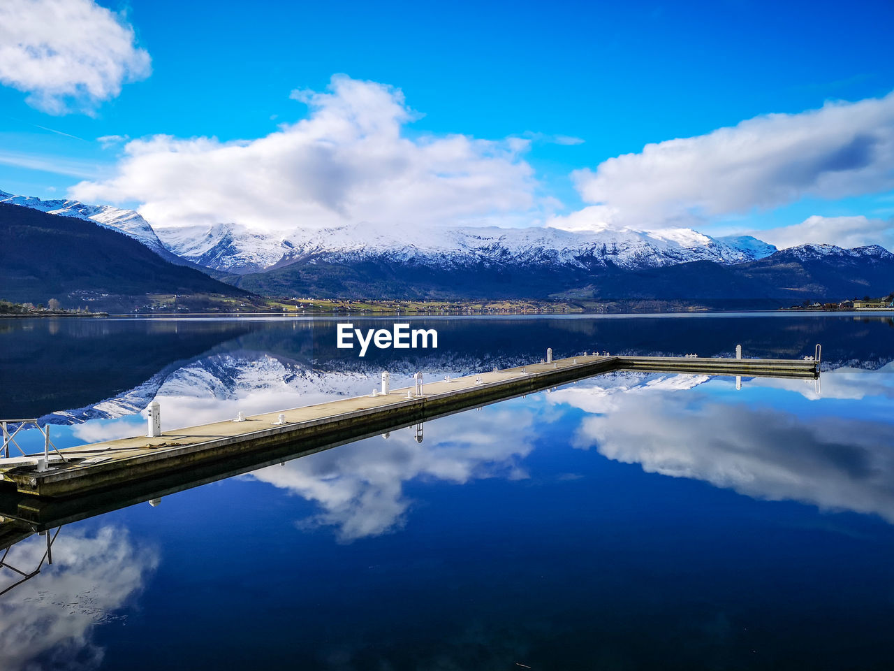 Scenic view of a boat dock in norwegian fjord and mountains against blue sky