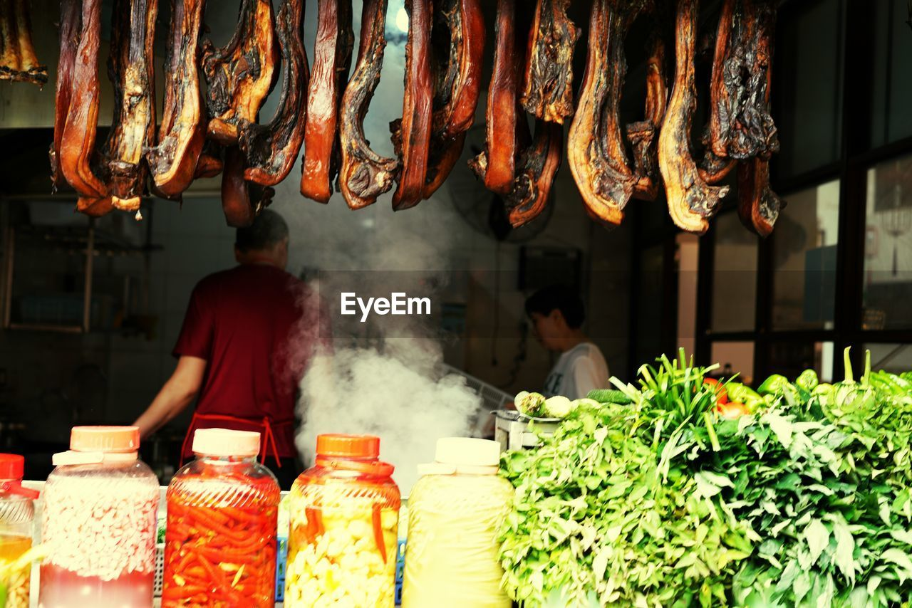 food and drink, food, meat, market, freshness, for sale, real people, retail, market stall, large group of objects, business, one person, wellbeing, abundance, choice, arrangement, incidental people, barbecue, retail display, preparation, preparing food
