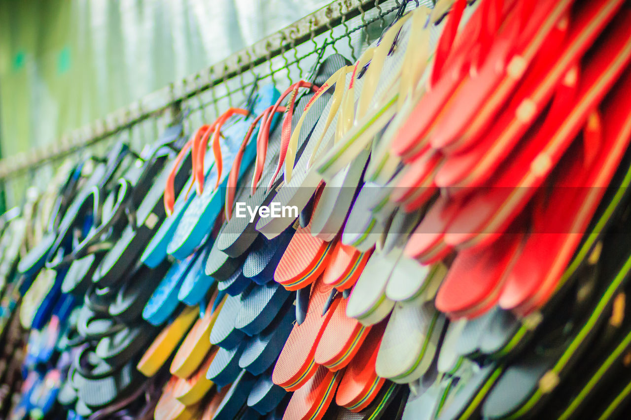 Low angle view of multi colored slippers hanging in market for sale