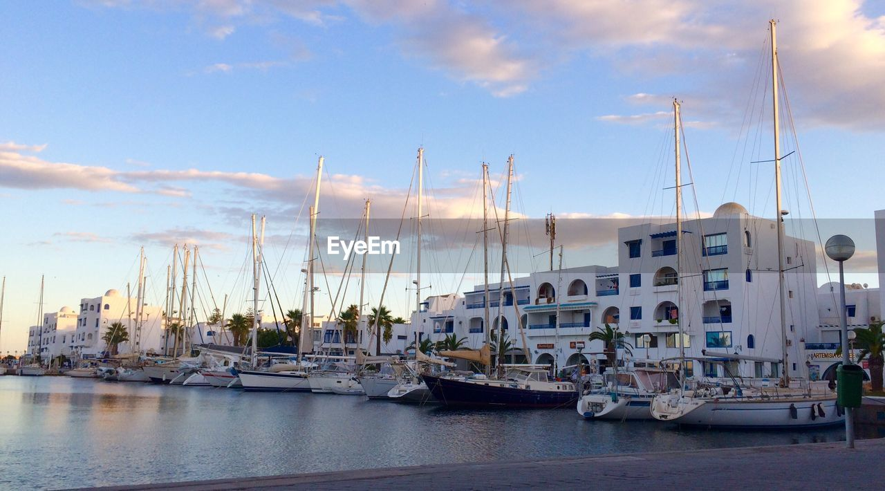 Boats Moored At Harbor In City Against Sky