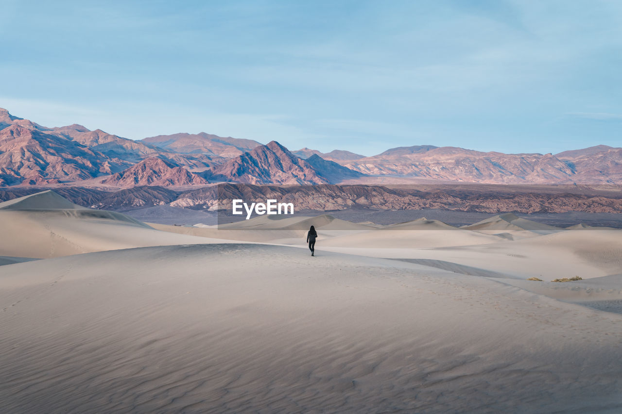Woman Walking On Desert Against Sky